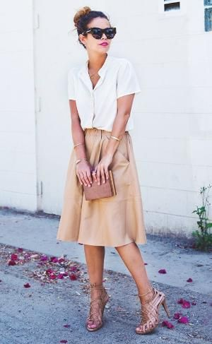 Sara of Collage Vintage wearing a button-up blouse tucked into a leather midi skirt with tan lace up heels by regina