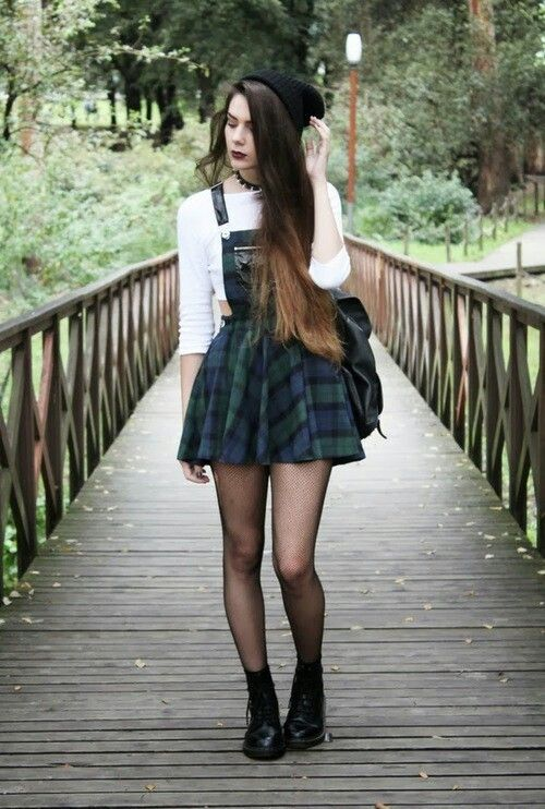 90s grunge-inspired: black beanie, plaid overall/skirt, white crop top, fishnets, doc martens