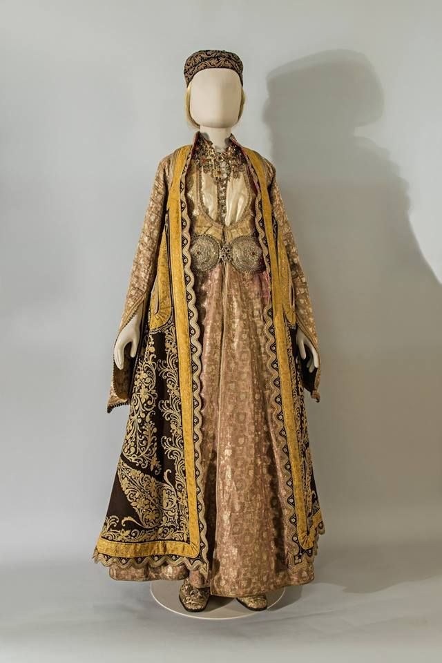 FESTIVE COSTUME Including a silk brocade dress and an overcoat, richly embroidered with gold thread. Epirus. Silk fabric, metal thread, cotton, wood and leather (shoes), velvet, gold plated silver and semi-precious stones (jewellery). 19th c.