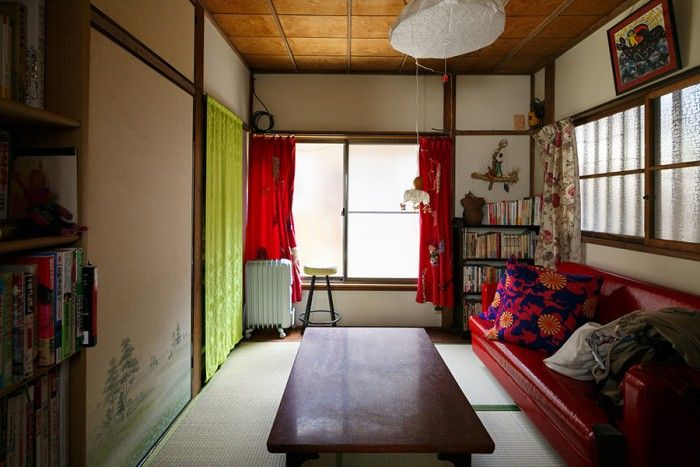 1階の間取りはこちらの4畳半とトイレのみ。畳にソファやカーテンの赤がよく映える。