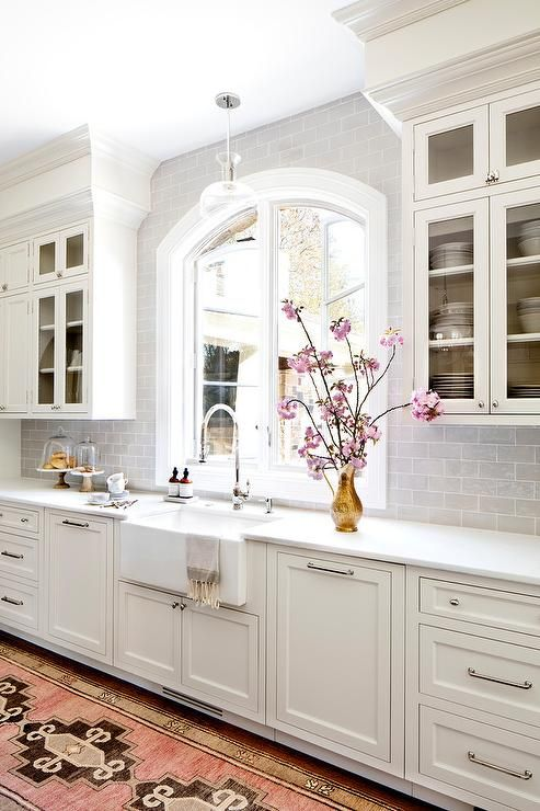 A pink and brown vintage runner sits in front of a farmhouse sink fitted with a polished nickel gooseneck faucet mounted to a white quartz countertop accenting white shaker cabinets adorned with nickel hardware.