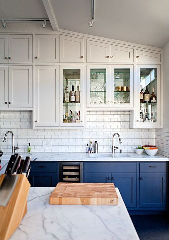 Painting the cabinets below the counters is a subtle way to infuse color into an otherwise all-white kitchen.