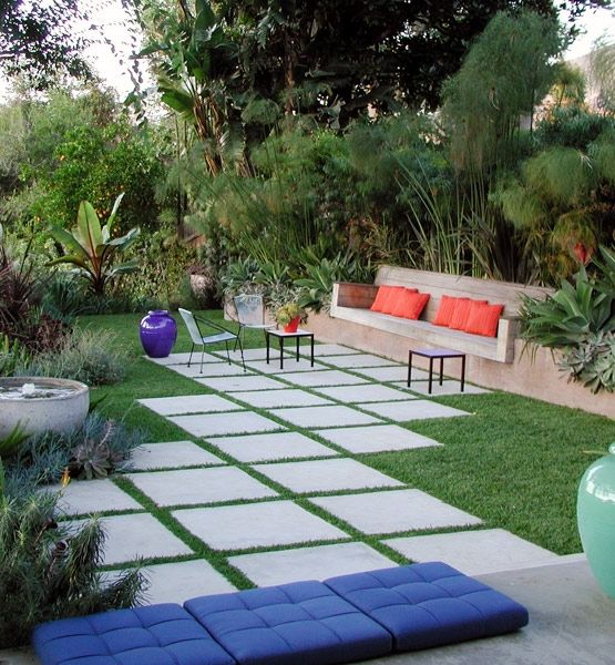 Elysian Landscapes transformed this simple backyard space into an open-air living room. Similar to an interior palette, the green in the surrounding landscape provides a background color, while blue and coral cushions offer bright accents.