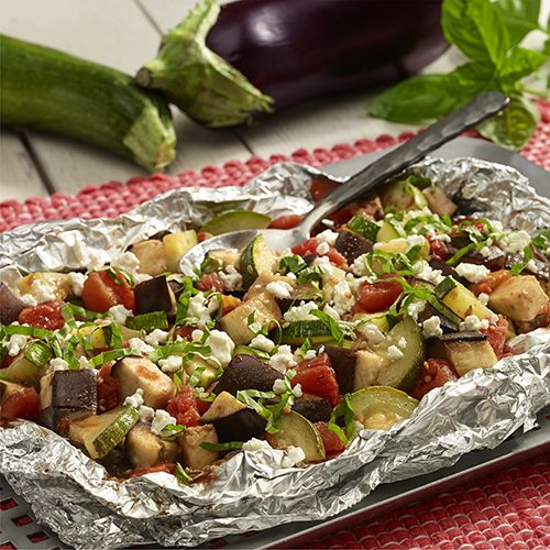 A grilled foil packet recipe with eggplant, zucchini and tomatoes combined in a foil packet and topped with fresh basil and goat cheese for a simple side dish