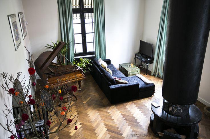 Zwarte kozijnen, groene gordijnen, witte muren en een piano met een plant.  Huizentour in het monumentale pand van Claire