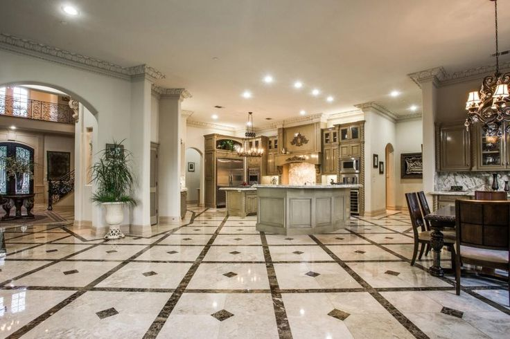 Upon entering the home, a lovely archway leads from the foyer to the open concept kitchen and dining area. A luxurious marble floor laid in a diamond pattern carries throughout the space, uniting the first floor.