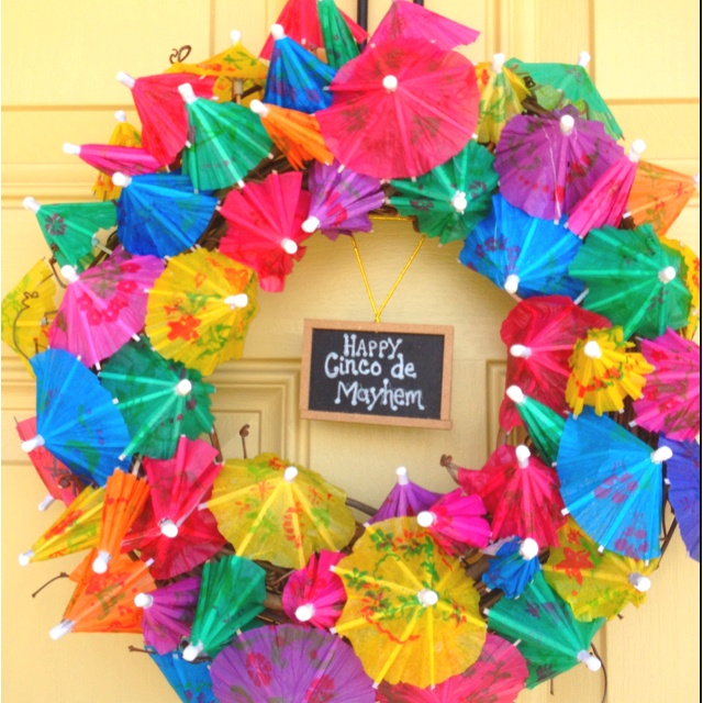 Stick drink umbrellas in a craft wreath for a pool/beach/tiki/tropical party decoration.
