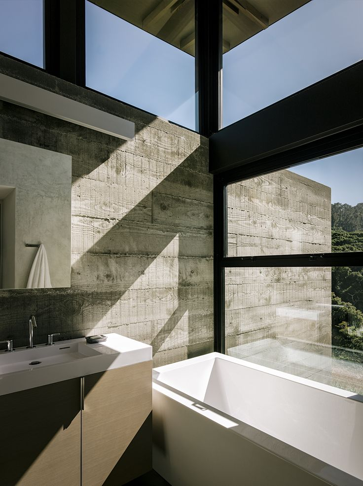 "The bathroom in the guest pavilion takes advantage of the passive solar siting. ""Detaching the roof from the walls allowed us to bring in light from the top,"" notes the architect. The custom vanity holds a Lacava sink; the tub is AquaStone from Aquatica."