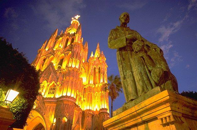 05 - Los reflectores iluminan La Parroquia de San Miguel Arcángel en la noche. La estatua de Fray Juan de San Miguel se encuentra en frente de la Plaza Principal de San Miguel de Allende, México.