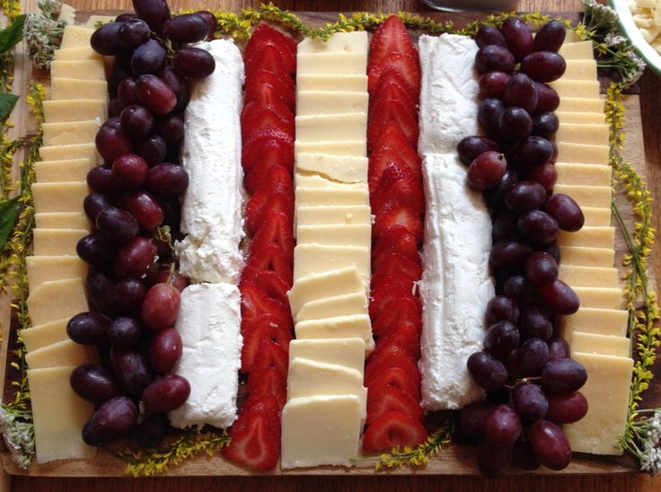 A simple cheese tray: three different cheeses separated by strawberries and grapes adorned with wild flowers. Easy and simple to pair with any complimentary wine!
