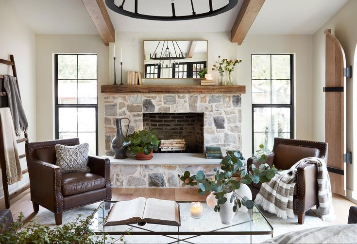 This stonework on the fireplace brings in the same natural feeling to the interior of this home as it does on the exterior. We tied in the earthy tones of the Mediterranean style with the raw wood mantel and modernized the whole look with black window frames and black statement chandeliers.