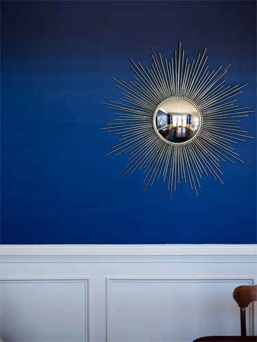How to Decorate with Blue: Set off the look of a bold blue wall a gold accent piece, like this sunburst mirror #diy #color #decorideas