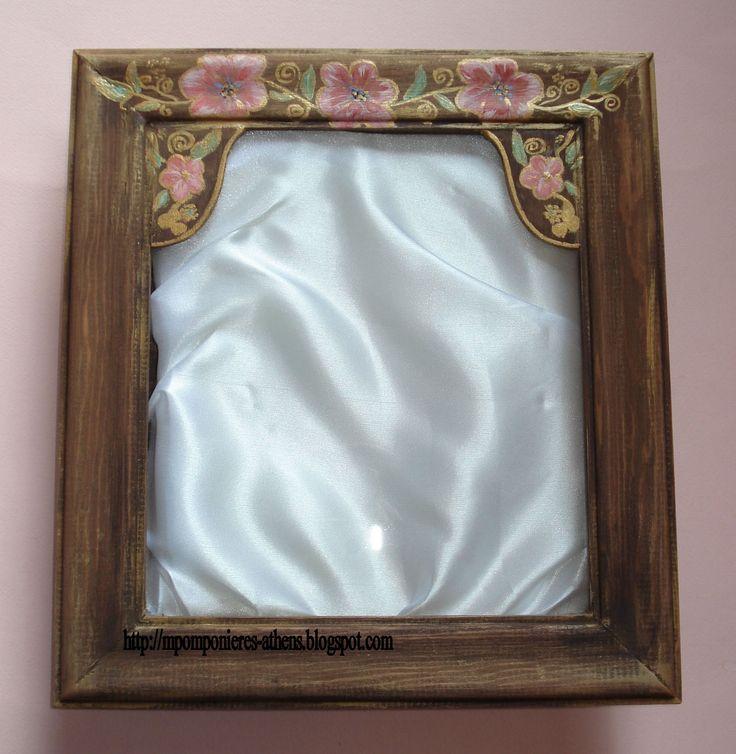 Στεφανοθήκη λουλουδάκια  Χειροποίητη στεφανοθήκη με ζωγραφισμένα ροζ λουλουδάκια με χρυσά και πράσινα κλαδιά και φύλλα. Διατίθεται με εσωτερική επένδυση σατέν ή δαντέλα στα χρώματα της επιλογής σας. Διαστάσεις 31Χ33cm.  Τιμή: 85.00 €