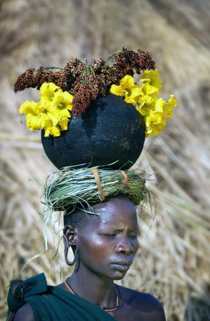 Africa |  Suri woman carrying a bowl of flowers on her head.  Omo Valley, Ethiopia | ©Piper Mackay