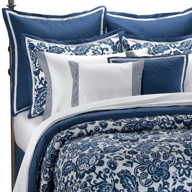 Blue and white bedding with a white coverlet
