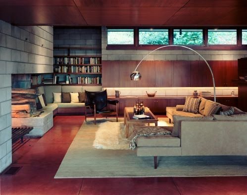 Interior of living room with dark colours and modern style    Love this living area, beautiful warm jarrah- lots of functional storage and coloured concrete flooring