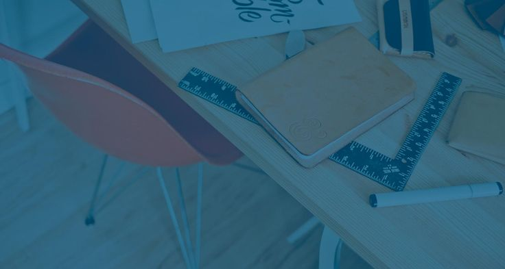Skrivbord i trä med anteckningsblock, linjal och penna ovanpå