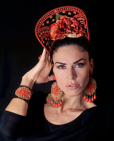 A model with a beautiful red peineta and matching jewellery