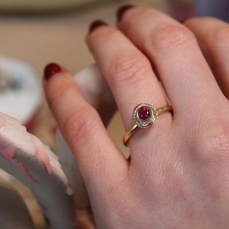 An elegant ring by Andrew Geoghegan, with a brilliant cut ruby surrounded by undulating waves of pink sapphires and white diamonds set in yellow gold. Discover the best gemstone for a coloured engagement ring, whether it is traditional or not traditional in design for wedding and bridal season: http://www.thejewelleryeditor.com/bridal/article/sapphire-engagement-rings-number-one-coloured-gem/ #jewelry #teaparty