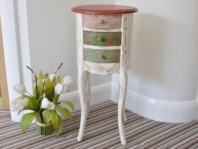 this small round distressed painted bedside table is finished in washed out greens and reds