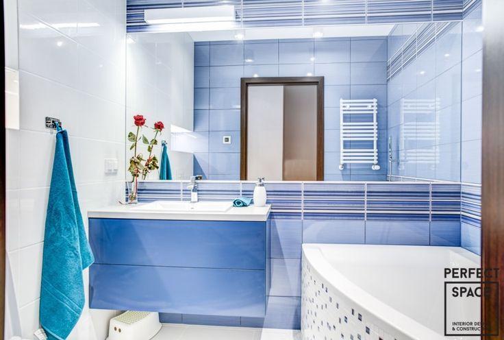 Niebieskie wnętrze łazienki, gdzie niebieskie są nie tylko płytki ale również meble łazienkowe i dodatki. Duże lustro optycznie powiększające przestrzeń łazienki to idealne rozwiązanie do małych pomieszczeń.