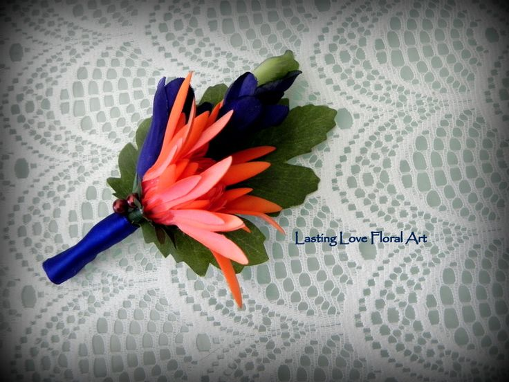 A real touch mum in orange and silks in blue make this bold boutonniere pop!  #blueandorangewedding #blueandorangeweddingflowers #orangeandbluewedding #orangeandblueweddingflowers  #orangeandbluebouquet #blueandorangebouquet #orangewedding #bluewedding #weddingflowers