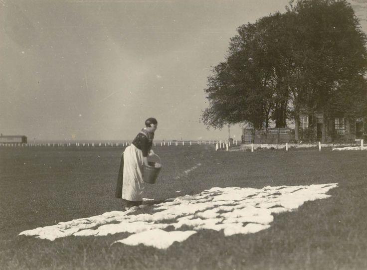 Een vrouw in streekdracht uit Harderwijk bleekt de was op een bleekveld. 1926 #Veluwe #Gelderland #Saksen