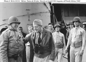"""Major General George S. Patton, Jr., U.S. Army, Commanding General, Western Task Force, U.S. Army (left); and Rear Admiral H. Kent Hewitt, USN, Commander Western Naval Task Force, (centre) share a light moment on board USS Augusta (CA-31), off Morocco during the Operation """"Torch"""" landings.  Though the original photo is dated 4 December 1942, it was probably taken shortly before MGen. Patton went ashore on 8 or 9 November 1942."""