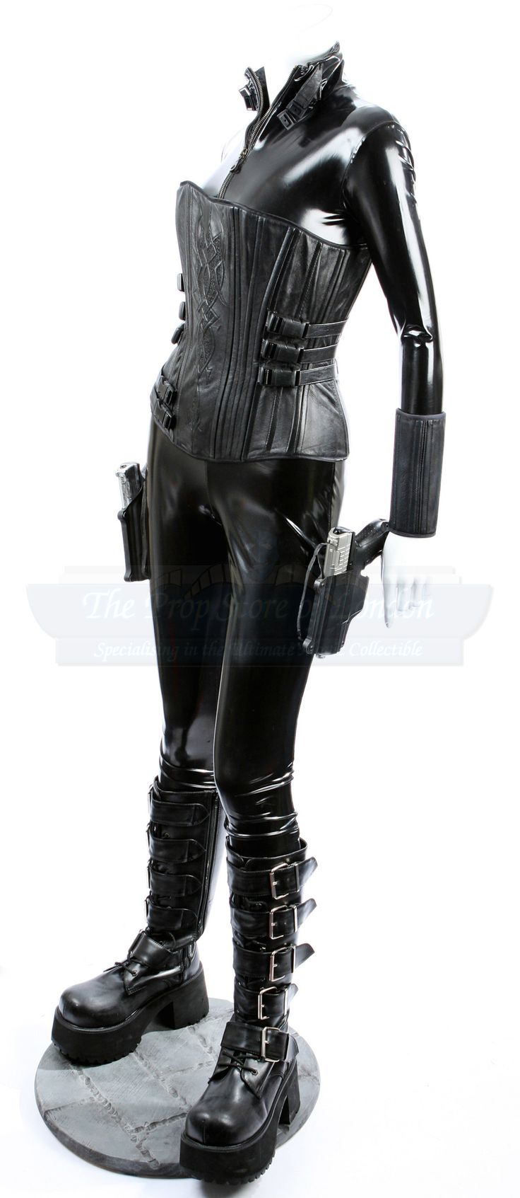 Skintight black bodysuit w zipper closure from the neck to lower torso. Also black leather zip-up arm gauntlets.   Black leather corset has lace-up back and double zipper. 8 leather straps extend around the side and clip to corset front.  2 black gun holsters attach to the outside of the upper thighs using small, high powered magnets.  The calf-high black leather platform boots have laces and zipper all the way up and 5 buckles.