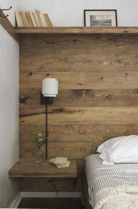By adding simple paneling made from floor boards: built-in shelf, bedside table, & hook rack, ... defined & maximized the space.