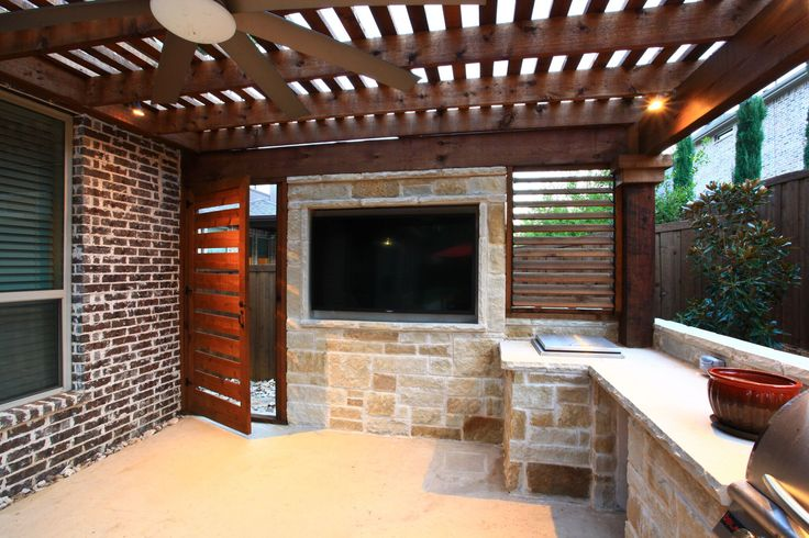 Beautiful door opens into the outdoor kitchen. Perfect for watching TV under the shaded arbor while cooking in the green egg or BBQ. By Outdoor Signature in Argyle, TX.