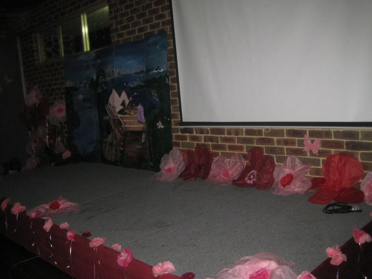 Stage decorated with hundreds of flowers, the hand painted mural and a screen where we played video