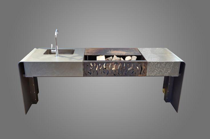 Hier ist unsere R2 Aussenküche mit offener Feuerstelle und Grauwackearbeitsplatte zu sehen. Waschbecken auch aus Naturstein. Hochwertige Armatur der Firma Dornbracht. Modernes Design von Rheingrün Living. Individuell zusammenzustellen. Zu sehen in unserem Showroom im Kölner Rheinauhafen.