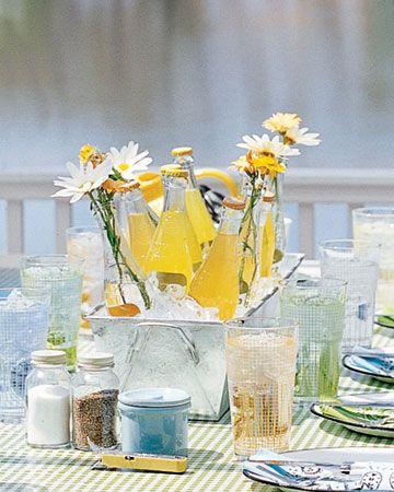 Zinkwanne mit Eis, Getränken und frischen Blumen als sommerliche Tischdeko.