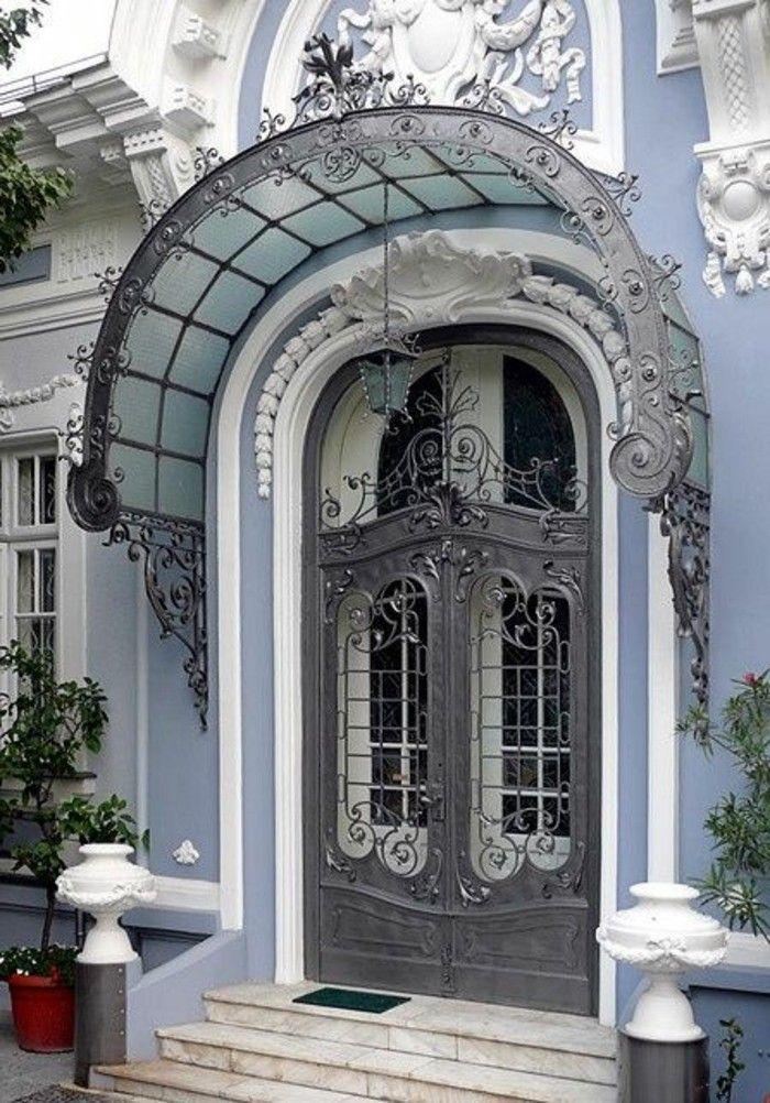 grille fer forgé, volutes et fleurs, ornements en plâtre sur la façade, auvent de la porte d'entrée