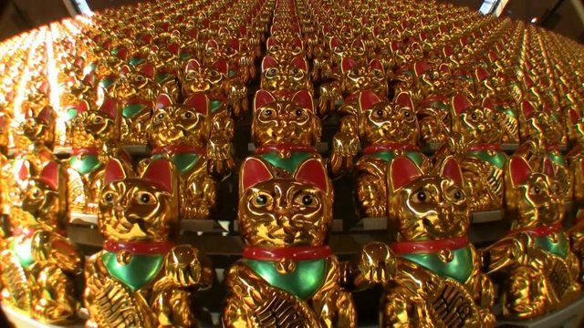 The Maneki Neko (jap., literally Beckoning Cat; aka Lucky Cat, Money Cat) is a common Japanese figurine which is believed to bring luck, attract customers and bring prosperity. The Lucky Cat waves with the raised left paw and holds a historic coin in front of itself with the right one. The Lucky Cat as talisman and selling product is wide-spread in Asia and meanwhile almost all over the world. Luck is associated here with monetary and material prosperity. For tourists the Lucky Cat became…