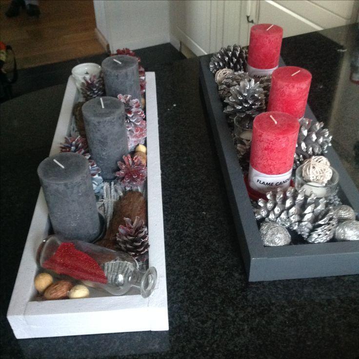 Kerstdecoratie wit met grijze kaarsen en rode accenten.