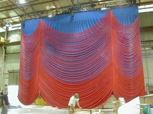 """This is the Hairspray curtain being fabricated in the shop....  """"Responding to David Rockwell's design of a """"Flip"""" Main Curtain for Hairspray on Broadway, I. Weiss hand-stitched 27,000' of red silicon tubing in 350 pieces to a velour Austrian Curtain. The Austrian was attached to a steel frame to help hold its shape and support the enormous weight of the entire show curtain - altogether 2,250 lbs."""" Show Curtains"""