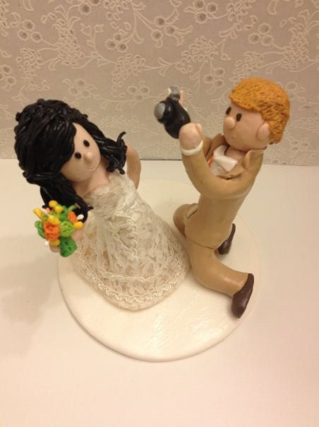 Custom Made Cake Topper With The Groom Holding A Camera And Kneeling To Take Picture