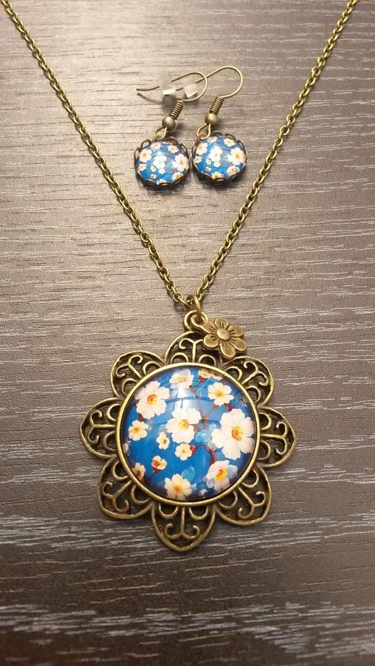 Bronzen halsketting met blauw witte bloemetjes in een bloemvormige medaillon.