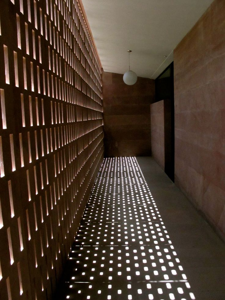 The corridor of Rass Haveli Hotel, Jodhpur, India hallway with perforated carved stone screen wall dappled light effect