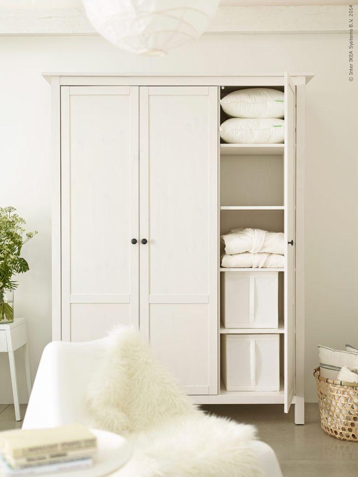 HEMNES klädskåp i vitbetsat massivt trä har tre dörrar och flyttbara hyllplan. SKUBB låda, HÖJDARE korg, IKEA PS VÅGÖ fåtölj, LUDDE fårskinn.