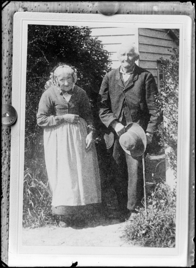 This couple would have been born around the 1830's-40's  Unidentified elderly couple outdoors, man holds a hat and cane and the woman wears a bonnet, probably Christchurch district