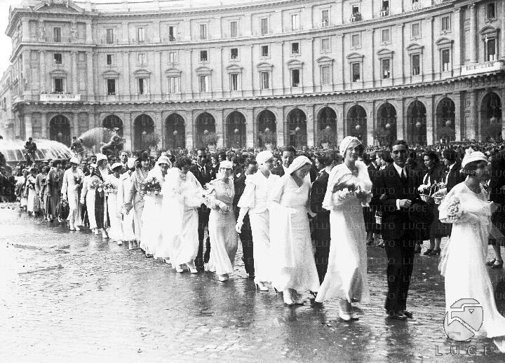 Processione di coppie di sposi in piazza Esedra in occasione della sagra della nuzialità 30.10.1933