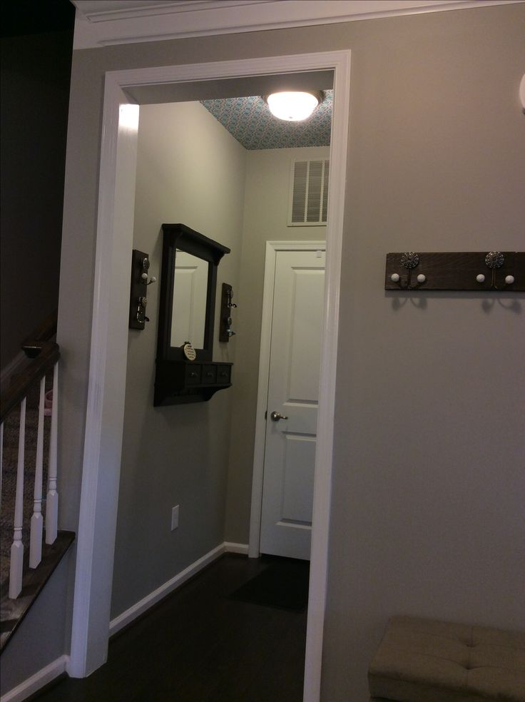 Ryan homes Rome model, mud room entryway, wallpaper on ceiling, sherwin williams mindful gray paint, purchased custom hooks installed on extra American scrape brown bear hardwood floor.
