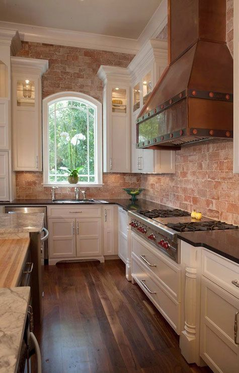 Beautiful kitchen with exposed brick walls framing copper hood over integrated Wolf Cooktop paired with pot and pan drawers flanked by white cabinets and black countertops over walnut floors.