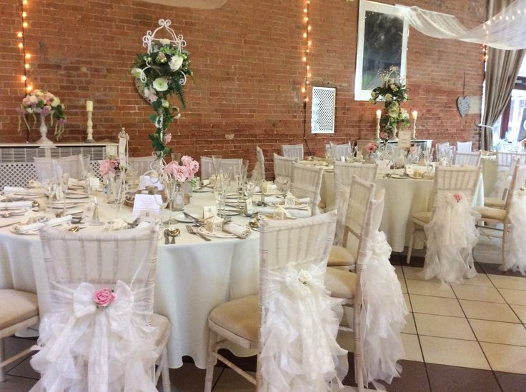 Pastel floral wedding breakfast decor with stunning chivari chairs with chiffon frill hoods and a lace bow with flower to the centre. www.elshamhallevents.co.uk