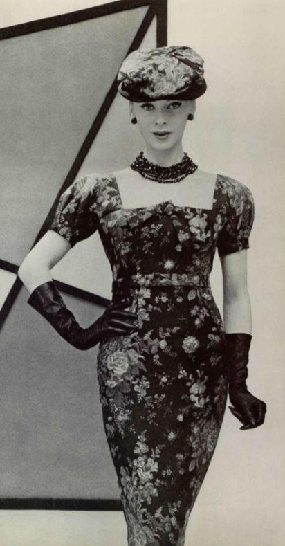 1956 Dior.D'une apparente simplicité, cette robe au corsage décolleté en carré, aux petites manches ballon, à la taille haute est l'exemple type de la ligne nouvelle. La jupe fourreau allonge la silhouette. Le tissu choisi est une soie imprimée