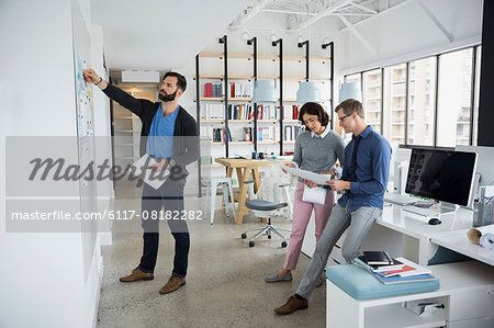 Architects meeting and discussing blueprints in office  – Image © Masterfile.com: Creative Stock Photos, Vectors and Illustrations for Web, Mobile and Print