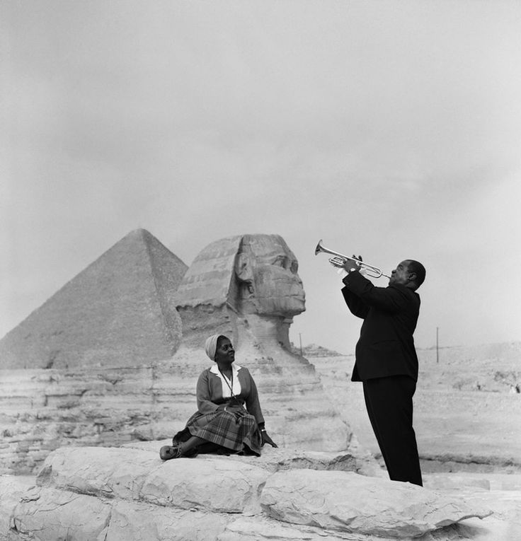 Louis Armstrong playing trumpet for his wife, Lucille, in front of the Great Sphinx and pyramids in Giza, Egypt.